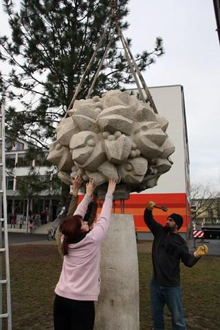 """Die Skulptur """"Vogelbaum"""" von Klaus Thiede wurde gestern auf dem Gelände der Grundschule """"Am Kannenstieg"""" wieder installiert. Rainer Dähre (verdeckt), Franziska Neubert und Thomas Wulf passen das tonnenschwere Betonstück ein. Foto: Stefan Harter"""