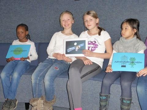 Vertreterinnen der 1a (Astronautengruppe), 1c (Sonnengruppe) und 4b (Satellitengruppe) präsentieren ihre Gruppenschilder.