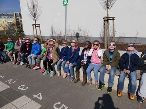 Die Sonnenkinder probieren die SoFi-Brillen schon einmal einen Tag früher im Klassenzimmer im Freien (Schachbrett) aus.