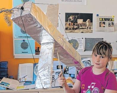 Marie aus der 4. Klasse präsentiert stolz den von der Klasse selbstgebastelten Satelliten. Foto: Vanessa Kanz