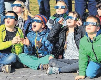 Gebannt blicken Schüler der Grundschule Am Kannenstieg auf ihrem Schulhof auf die sich verdunkelnde Sonne. So ein wunderbares Naturschauspiel sahen die Kinder zum ersten Mal. Foto: Viktoria Kühne