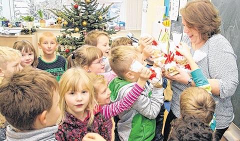 """Die Klasse 1c der Grundschule """"Am Kannenstieg"""" übergibt selbst gebackene Plätzchen und eine Geldspende an Hanna Klingenberg für die Kinder im Kinderhospiz. Foto: Stefan Harter"""